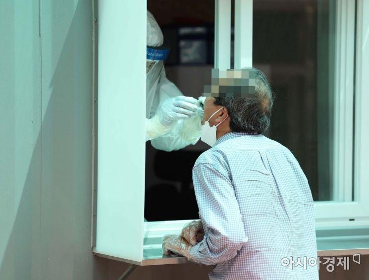 8일 서울 광진구보건소 신종 코로나바이러스 감염증(코로나19) 선별진료소 앞에 설치된 옥외 검체채취 부스에서 한 시민이 진료를 받고 있다. /문호남 기자 munonam@