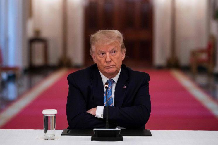 (워싱턴 AFP=연합뉴스) 도널드 트럼프 미국 대통령이 7일(현지시간) 백악관 이스트룸에서 열린 학교 수업 재개 회의에 참석해 팔짱을 끼고 앉아 있다.