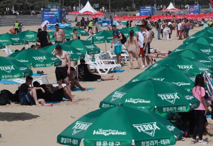 지난 5일 오후 부산 해운대구 해운대해수욕장에서 외국인들이 파라솔 아래 휴식을 취하고 있다. [이미지출처=연합뉴스]