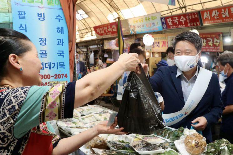 김학도 중소벤처기업진흥공단 이사장(오른쪽)이 지난 10일 서울 영등포 중앙시장에서 열린 '중진공이 전통시장과 가치합니다' 캠페인에 참여해 상인에게 음식을 구입하면서 활짝 웃고 있다.