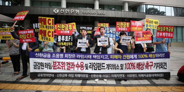 서울 중구 신한은행 본점 앞에서 라임자산운용 사모펀드 피해자들이 배상 촉구 구호를 외치고 있다. [이미지출처=연합뉴스]