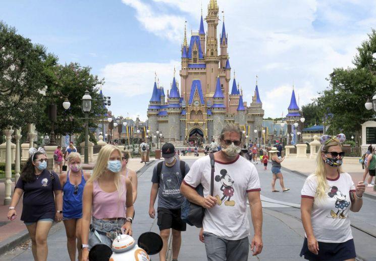 지난 11일(현지시간) 개장한 미 플로리다주 소재 월트 디즈니월드에서 입장객들이 마스크를 쓰고 있다. / 사진=연합뉴스