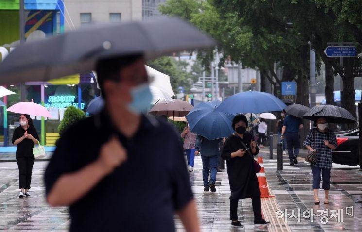 전국에 장맛비가 내린 13일 서울 세종대로에서 우산을 쓴 시민들이 발걸음을 재촉하고 있다./김현민 기자 kimhyun81@