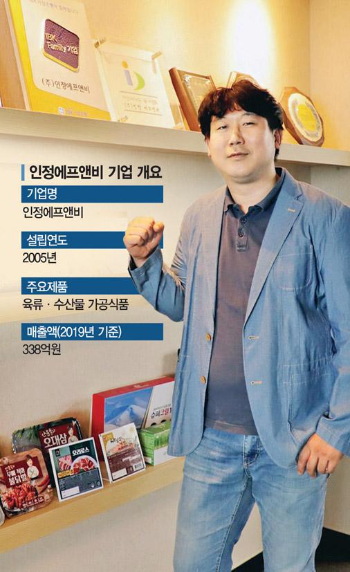 김명중 인정에프앤비 대표가 본사에 전시된 가정간편식 등 제품들 옆에서 포즈를 취하고 있다.