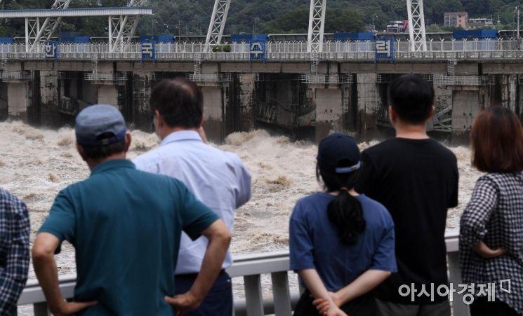 장마전선의 영향으로 닷새째 집중호우가 이어진 6일 경기 하남시 팔당댐에서 수문 15개 중 12개를 개방한 가운데 초당 만8천톤 가량의 물이 방류되고 있다. 오전부터 늘어난 팔당댐 유량이 한강에 영향을 미치면서 오전 11시부로 한강대교에 홍수주의보가 발령됐다./하남=김현민 기자 kimhyun81@