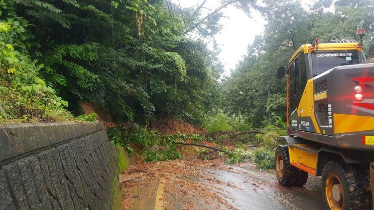 남부지방에 시간당 50㎜에 이르는 폭우가 쏟아진 8일 오전 부산 강서구 가덕도 도로가 산사태로 유실돼 긴급 복구작업이 이뤄지고 있다. [부산경찰청 제공]