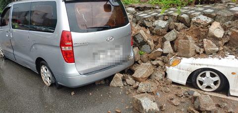 시간당 50㎜ 이르는 폭우가 쏟아진 8일 오전 부산 사하구 감천동 도로변 축대가 붕괴돼 주차된 차량이 매몰돼 있다. [부산경찰청 제공]