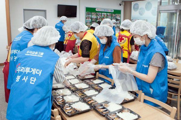 우리금융그룹 임직원 자원봉사단이 충북 충주시 충주봉사관에서 대한적십자사와 함께 전달할 음식을 직접 만들고 도시락을 포장하는 봉사활동을 펼치고 있다.