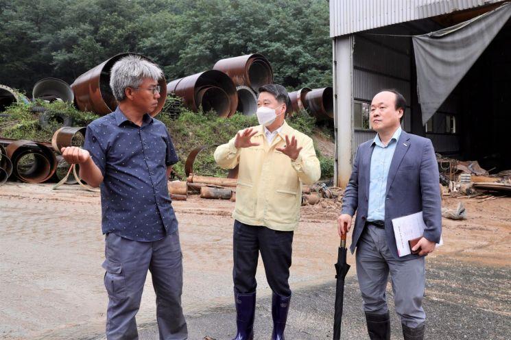 김학도 중소벤처기업진흥공단 이사장(가운데)이 지난 7일 충북 음성 소재 중소기업 '태성스틸' 수해 복구현장을 방문해 관계자들과 이야기를 나누고 있다.
