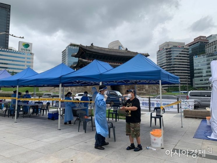 서울 중구 숭례문 앞에 설치된 선별진료소에서 한 남대문 시장 상인이 의료진으로부터 주의사항을 전달받고 있다./사진=김슬기 인턴기자 sabiduriakim@asiae.co.kr