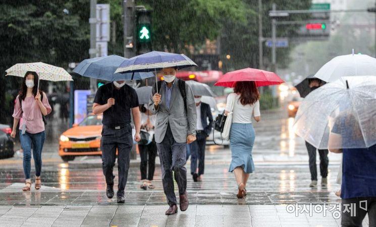 장마가 이어지고 있는 11일 서울 종로구 세종로 네거리에서 직장인들이 우산을 쓰고 출근길에 오르고 있다./강진형 기자aymsdream@