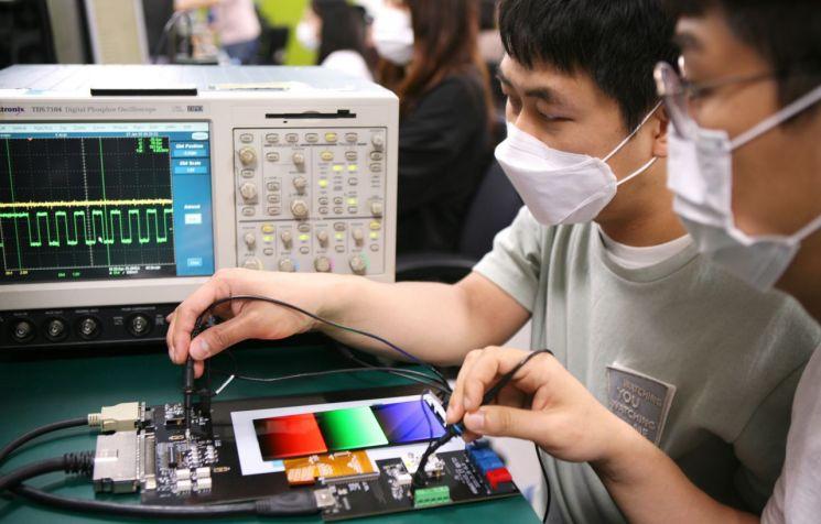 삼성디스플레이 개발자들이 '어댑티브 프리퀀시' 기술이 적용된 패널의 주사율 변화를 테스트 기기로 점검하고 있다.   [사진제공=삼성디스플레이