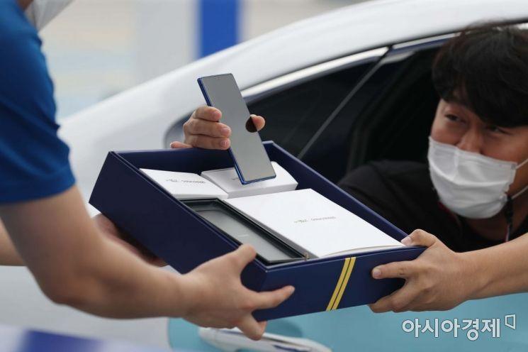 13일 서울 성동구 비트플렉스 야외 주차장에서 SK텔레콤 주최로 열린 '갤럭시노트20 5G 드라이브 스루 행사'에서 고객들이 갤럭시노트20을 받고 있다. /문호남 기자 munonam@