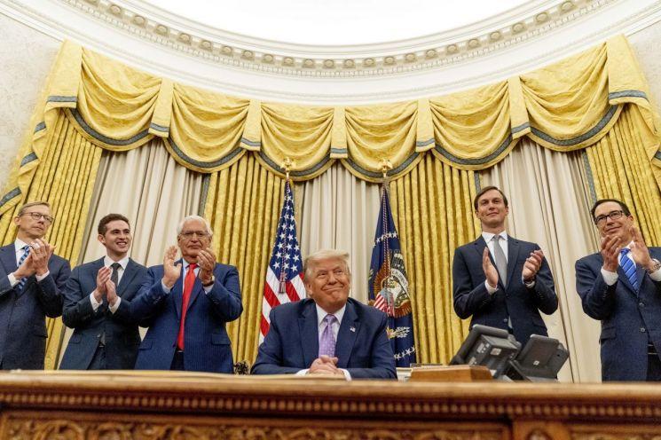 도널드 트럼프 미국 대통령이 이스라엘과 아랍에미레이트(UAE)간의 외교관계 체결에 대한 합의문 발표 후 집무실에서 측근들의 박수를 받고 있다. [이미지출처=AP연합뉴스]