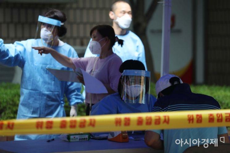 14일 서울 동대문 통일상가 인근에 마련된 신종 코로나바이러스 감염증(코로나19) 임시 선별진료소에서 의료진이 문진표 작성을 돕고 있다. /문호남 기자 munonam@