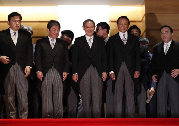 16일 밤 스가 요시히데 일본 총리(왼쪽에서 세번쨰)와 아소 다로 부총리 겸 재무상(왼쪽에서 네번째), 모테기 도시미쓰 외무상(왼쪽에서 두번째 등 새 내각 각료들이 사진 촬영을 위해 자리를 조정하고 있다. [이미지출처=EPA연합뉴스]