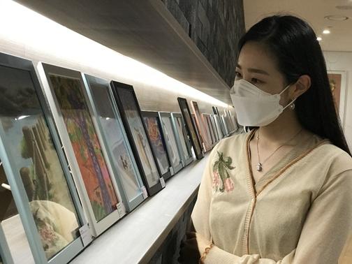 LG헬로비전 직원이 서울 상암동 사옥에 전시된 '자녀그림 콘테스트' 작품을 관람하고 있다.[사진=LG헬로비전 제공]