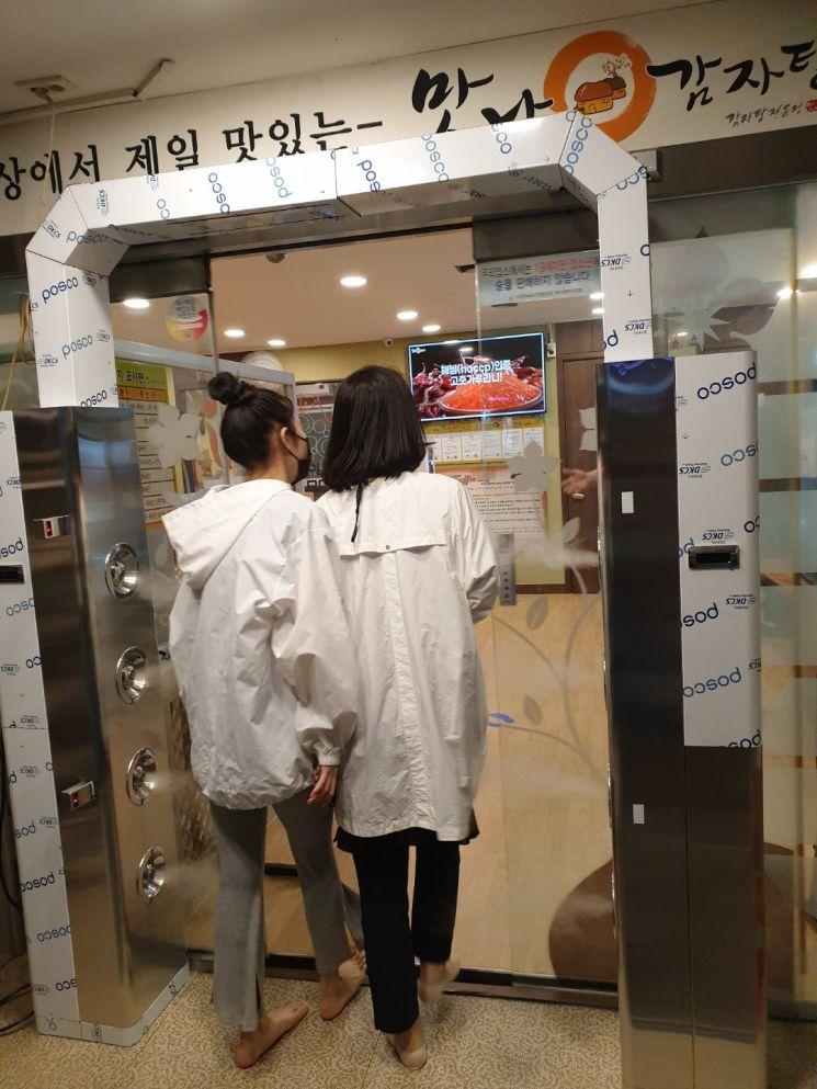 맛나감자탕 부산 화명점. 터널식 전신소독기가 매장 입구에 설치돼 방문객이 드나들 때마다 살균수를 분사해 바이러스 오염원을 제거한다.