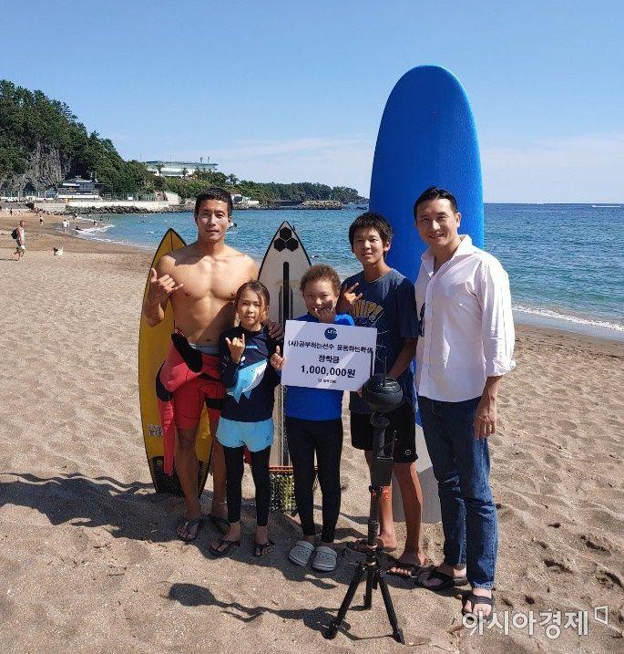 사단법인 공부하는 선수 운동하는 학생의 정규영 회장(맨 오른쪽)이 서핑 꿈나무인 제주 삼남매에게 장학금을 전달한 뒤 기념촬영하고 있다.