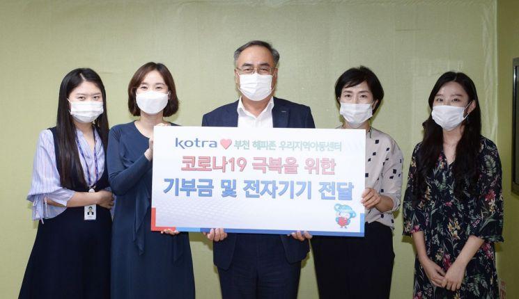 KOTRA가 25일 부천 '해피존 지역아동센터'를 찾아 교육용 전자기기와 임직원 기부금을 전달했다. 김종춘 KOTRA 부사장(가운데) 등 참석자들이 기부식에서 기념촬영을 하고 있다.
