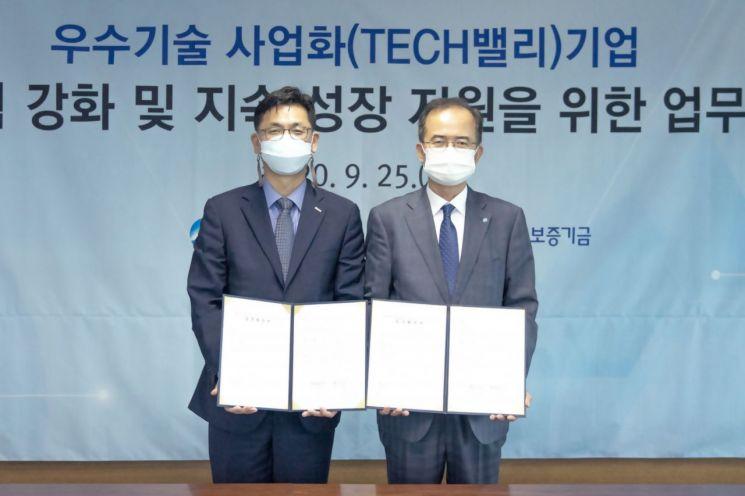 서동립(오른쪽) 우리은행 중소기업그룹장이 김영춘(왼쪽) 기술보증기금 이사와 기념촬영을 하고 있다.