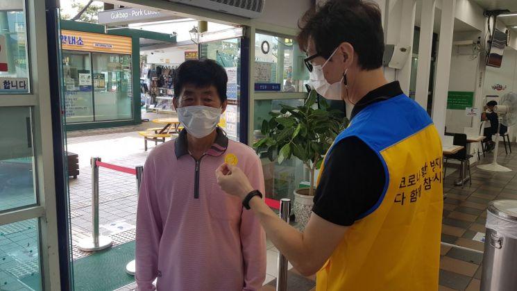 한국도로공사 경기광주지사 이천(하남)휴게소 직원이 고객의 체온을 측정한 뒤 스티커를 붙여주고 있다. (사진=한국도로공사)