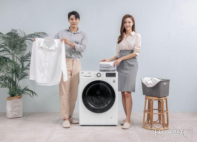 LG전자가 최적의 세탁방법을 알려주는 인공지능 DD(Direct Drive)세탁기 'LG 트롬 세탁기 씽큐'를 다음주에 출시한다. 모델들이 12kg 용량 LG 트롬 세탁기 씽큐(모델명: F12WVC)를 소개하고 있다.