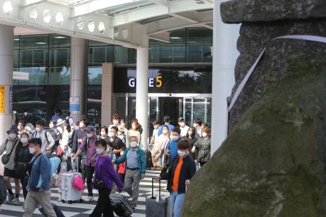 추석 연휴를 앞둔 주말인 지난 26일 제주에 도착한 관광객들이 마스크를 쓰고 제주국제공항을 빠져나가고 있다./사진=연합뉴스