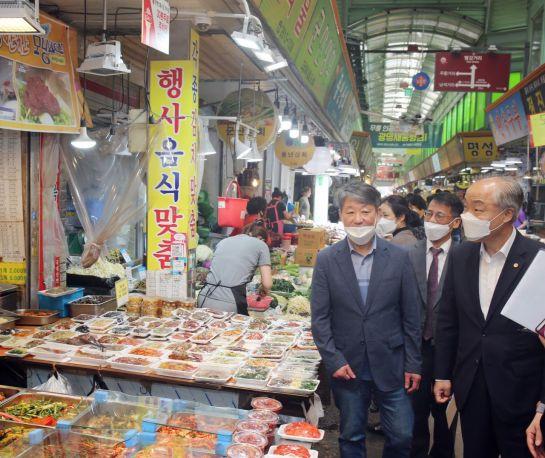 조봉환 소상공인시장진흥공단 이사장(오른쪽)이 전통시장을 방문해 관계자들과 점포를 살펴보고 있다.