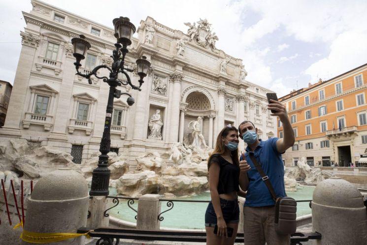이탈리아 로마의 트레비분수 앞에서 마스크를 쓴 커플이 셀카를 찍고 있다. [이미지출처=EPA연합뉴스]
