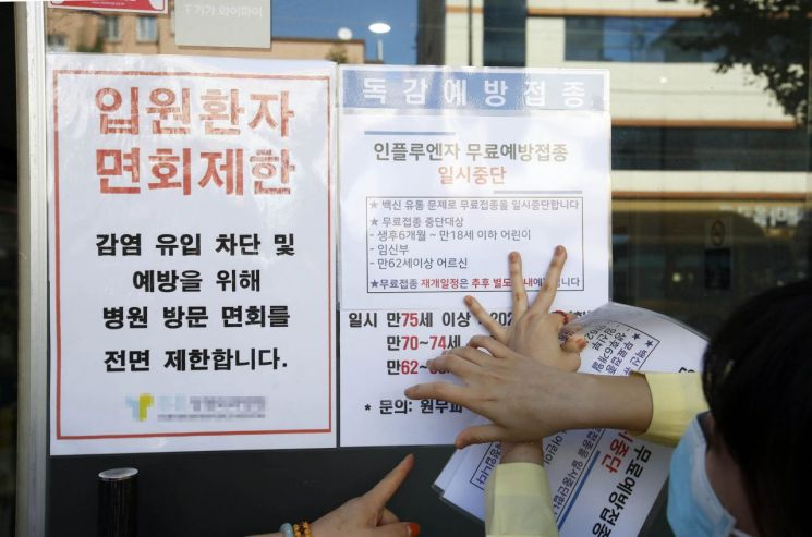 22일 오전 광주 북구의 한 병원에서 북구보건소 직원들이 인플루엔자(독감) 백신 무료접종 연기 안내문을 붙이고 있다. [이미지출처=연합뉴스]