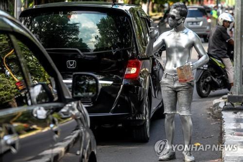 인도네시아에서 이동하는 차량에 구걸하는, 온 몸에 은색을 칠한 '실버맨'의 모습. [사진출처=연합뉴스]