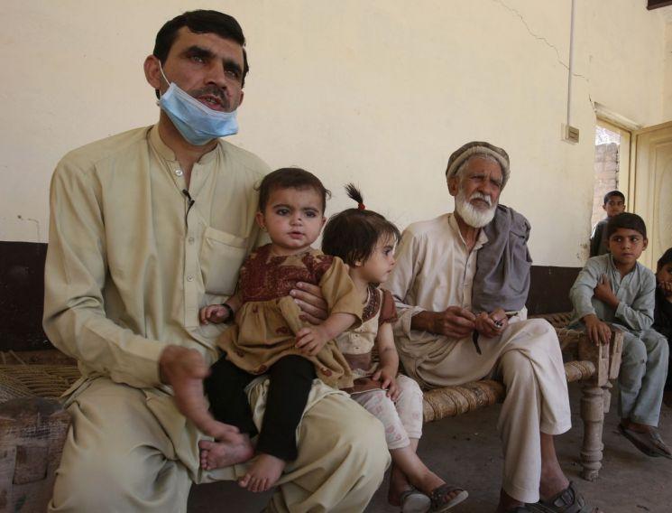 소아마비에 걸린 10달된 딸을 안고 있는 파키스탄 남성 [이미지출처=AP연합뉴스]