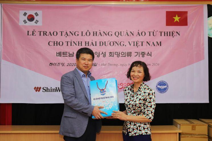 이규권 신원 베트남 2법인장(사진 왼쪽)이 의류 22만장 기부 후 베트남 하이즈엉 성 부녀협회 관계자와 기념촬영을 하고 있다.