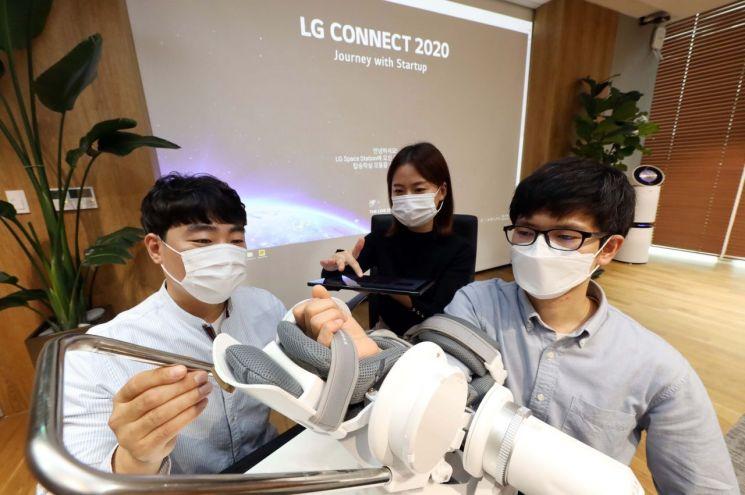 스타트업 행사 'LG 커넥트'에 참가한 에이치로보틱스 관계자가 재활 보조용 로봇 수트를 시연하고 있다.