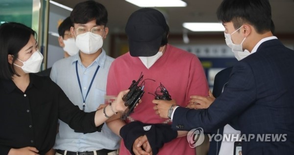 이른바 '서울역 묻지마 폭행 사건' 관련 상해 혐의를 받고 있는 남성이 지난 6월4일 오전 추가조사를 받기 위해 서울 용산구 용산경찰서에서 철도특별사법경찰대로 이송되고 있다. [이미지출처=연합뉴스]