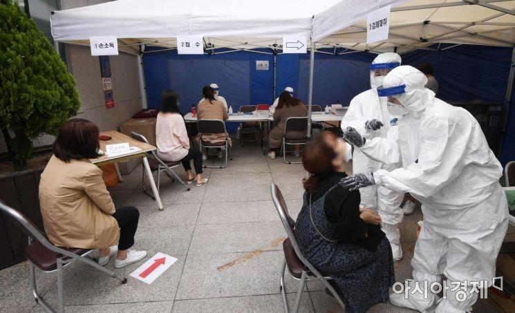 21일 서울 강남구 대치2동 주민센터 앞에 설치된 신종 코로나바이러스 감염증(코로나19) 임시 선별진료서에서 관내 학원강사들이 진단검사를 받고 있다. /김현민 기자 kimhyun81@