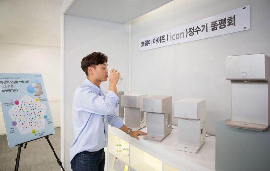 코웨이 직원이 '아이콘 정수기' 품평회에서 물을 마시고 있다.