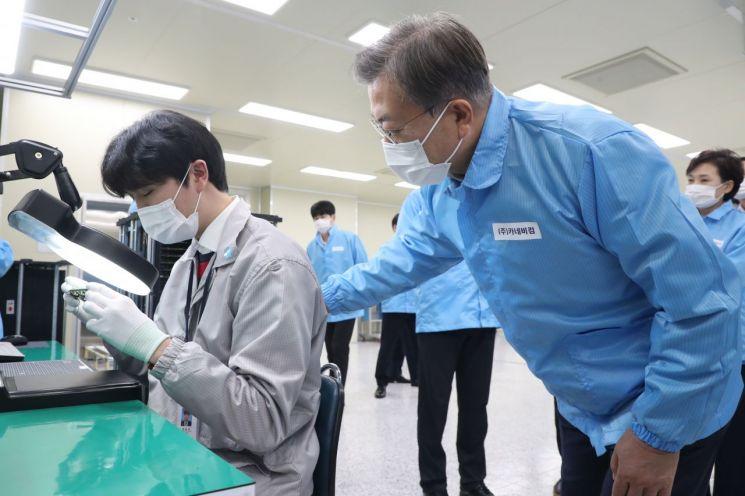 문재인 대통령이 22일 오후 디지털 SOC기업인 인천시 연수구 카네비컴을 방문해 불량품 검사하는 직원을 격려하고 있다.
