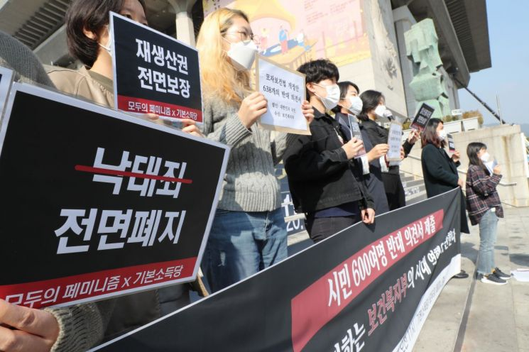 기본소득당과 모두의 페미니즘 관계자들이 19일 서울 종로구 세종문화회관 계단에서 보건복지부의 모자보건법 개정안을 규탄하는 기자회견을 하고 있다. [이미지출처=연합뉴스]