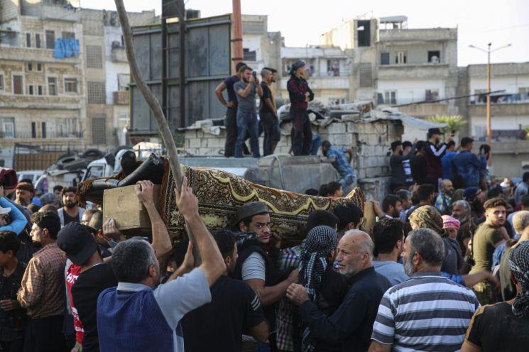 26일(현지시간) 시리아인들이 폭격으로 목숨을 잃은 이들의 장례식을 치르고 있다. [이미지출처=AP연합뉴스]