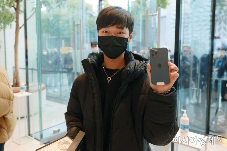 애플의 첫 5G 스마트폰 아이폰12 시리즈가 국내 공식 출시한 30일 서울 강남구 가로수길 애플스토어에서 구매 고객이 제품을 들어보이고 있다./김현민 기자 kimhyun81@