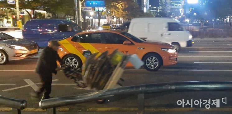 서울 한 번화가 도로에서 한 노인이 폐지가 가득 실린 손수레를 위태롭게 끌고 가고 있다. 사진=한승곤 기자 hsg@asiae.co.kr.