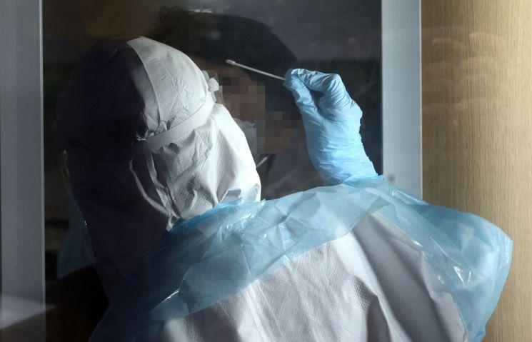 서울 성동구보건소에 마련된 선별진료소에서 의료진이 검체를 채취하고 있다. [이미지출처=연합뉴스]