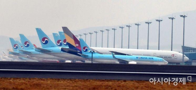 대한항공의 아시아나항공 인수가 추진되는 가운데 17일 인천국제공항 제4활주로 공사현장 뒤로 대한항공과 아시아나항공 여객기들이 세워져 있다. 2020 11. 17