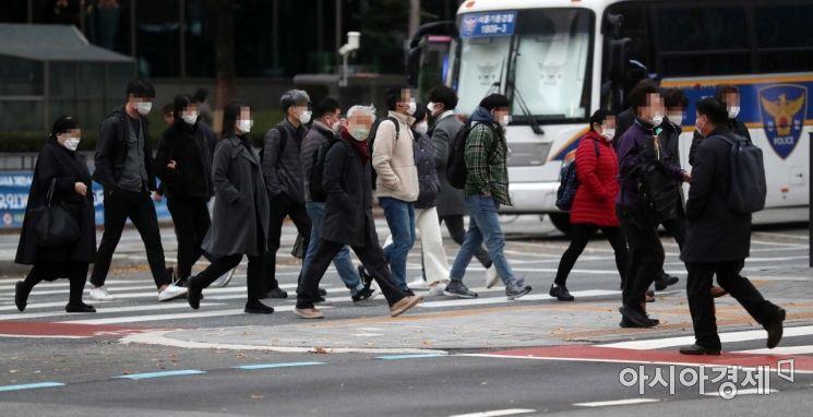 초겨울 추위가 찾아온 지난 20일 서울 종로구 광화문 사거리에서 두꺼운 옷을 입은 시민들이 출근길 발걸음을 옮기고 있다.