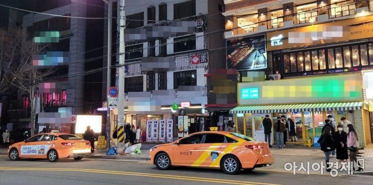 사회적 거리두기 2단계가 시행된 첫날인 24일 0시10분께 서울 마포구 홍익대학교 인근 거리. 자정이 지나 술집에서 나온 시민들이 택시를 잡기 위해 삼삼오오 모여 있다. 사진=유병돈 기자 tamond@