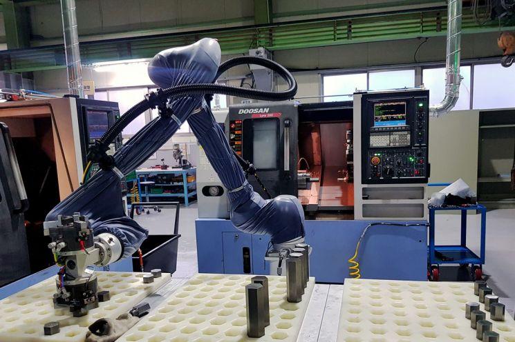 ㈜두산이 협력사 스마트공장 구축을 위해 도입한 협동로봇이 생산현장에서 작업을 수행하고 있다.  [사진제공=㈜두산]