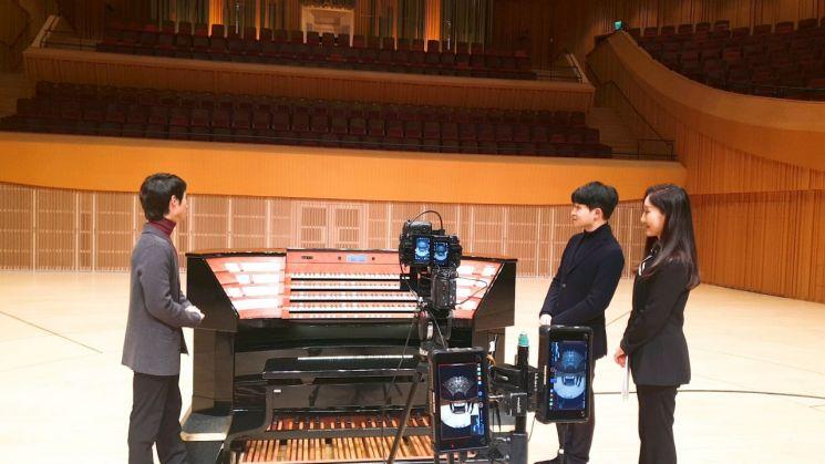피아니스트 선우예권(가운데)이 김시진 롯데콘서트홀 하우스 매니저(오른쪽)와 함께 오르가니스트 박준호로부터 롯데콘서트홀의 파이프 오르간에 대한 설명을 듣고 있다.  [사진= 롯데문화재단 제공]
