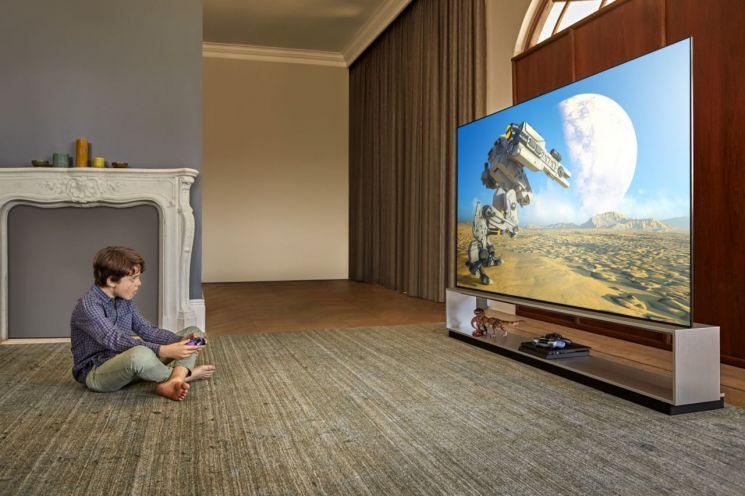 LG전자 모델이 LG 올레드 TV를 활용해 게임을 즐기고 있다.